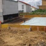 """Unser zur Hälfte abgedeckter Teil des Grundstückes; links wurde Beton in einen """"Graben"""" gegossen; aus dem Heizungsraum führen bereits Leitungen zu uns."""