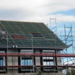 Die ersten Dachsteine sind gesetzt - auch zu sehen: die Dachrinnen sind (horizontal) fertig