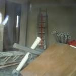 Verputztes und vollgestelltes Wohnzimmer - offenbar ist der Putz schon trocken, sonst würde da keine Leiter an der Wand lehnen