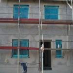 Fertig gedämmte Vorderseite des Hauses mit abgedeckten Fensterscheiben
