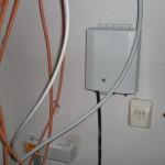 Großer Kasten der Telekom mit zugeführten Kabel durch das Leerrohr und über zwei Drähte angeschlossene Telefonbuchse