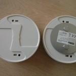 """Rechts die Unterseite eines Melders mit Magnetplatte, links noch einer ohne - ich habe die Platte so angebracht, dass zumindest der Teil mit den beiden Magneten komplett """"aufklebt"""""""